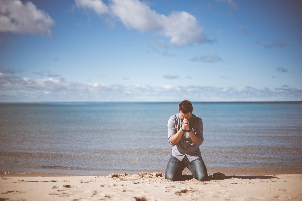 help men talk about their feelings. a picture of a man praying on a beach