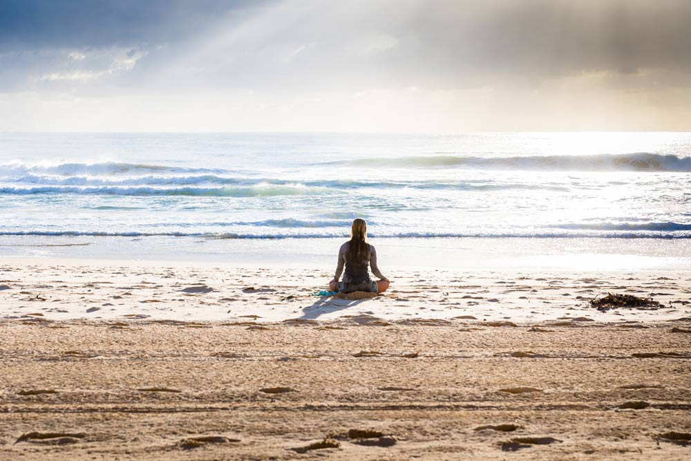 Start meditating. picture ofa woman meditating on a beach
