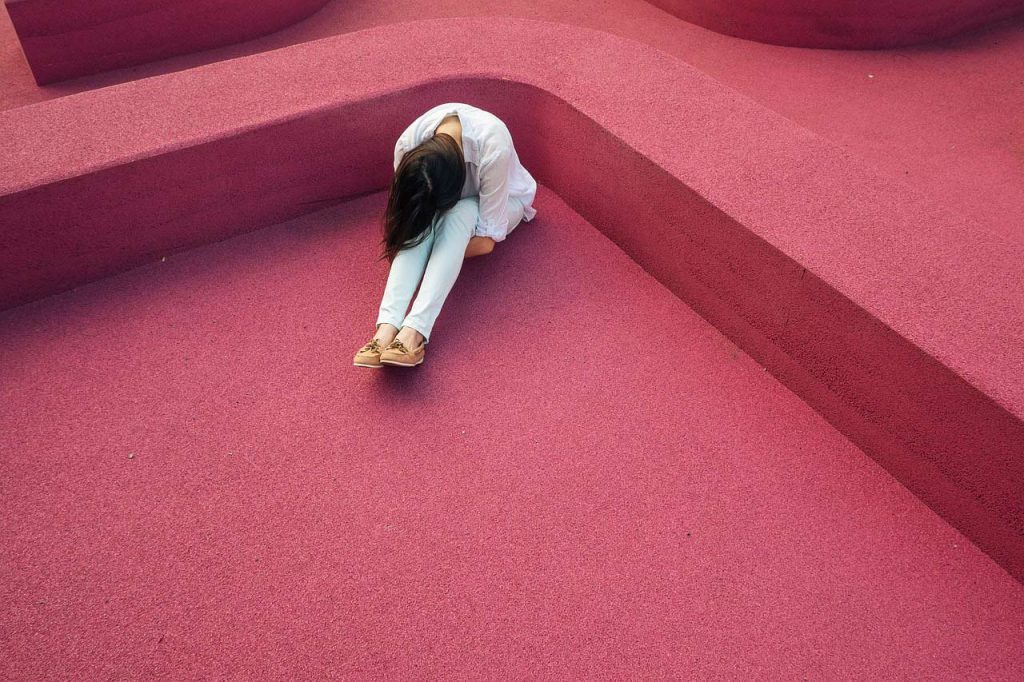 starting meditating can help relieve stress and depression. picture of a depressed person on a red floor