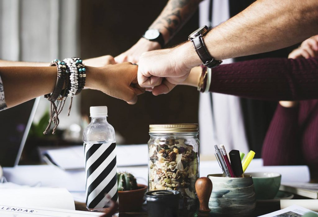Fist bump at a happy workplace. start to change your career direction