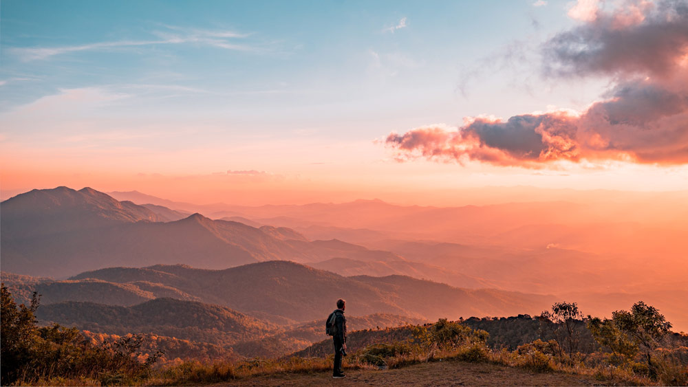 types of hypnotherapy represented with a man looking into the distance of a landscape